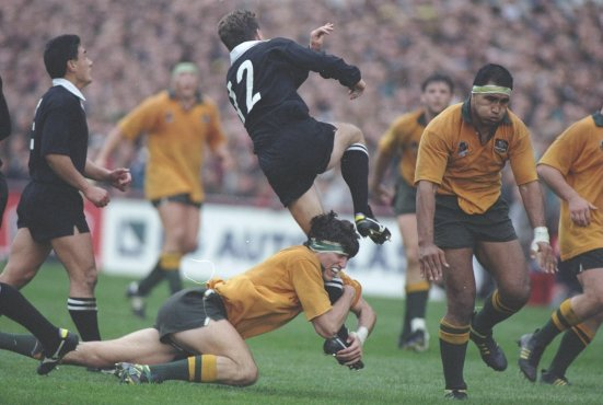 John Eales of Australia tackles Bernie McCahill of New Zealand. Eales has his arms wrapped around McCahill's left leg, while he jumps in the air.