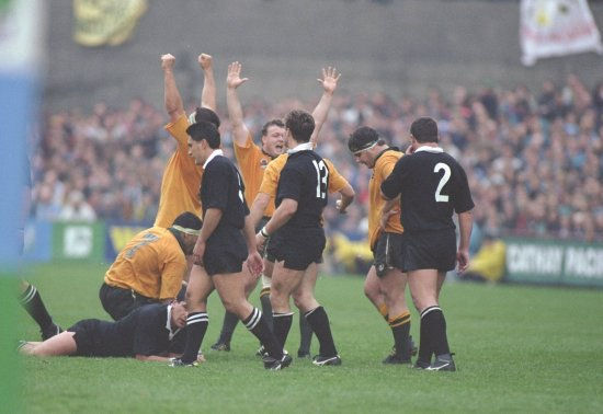 4 members of the New Zealand team look dejected while 5 members of the Australia team celebrate their Rugby World Cup semi-final win